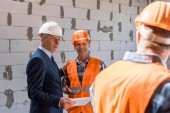 selective focus of builder and businessman looking at constructor