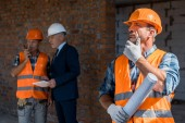 selective focus of builder holding blueprint near coworker and businessman