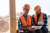 handsome middle aged man holding digital tablet near bearded coworker