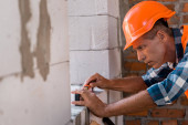 selective focus of middle aged constructor in helmet measuring concrete wall
