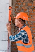 middle aged architect in helmet measuring concrete wall