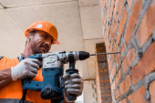 handsome man in earphones holding hammer drill near brick wall