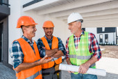 Fotografie happy constructors in helmets standing near coworker with blueprint