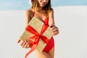 oříznutý pohled na sexy ženu v plavkách drží dárek na pláži v Maledivách
