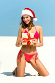 Fotografie sexy and smiling woman in santa hat and swimsuit holding christmas gift on beach in Maldives