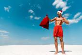 Fotografie pohledný a sexy muž v Santa klobouk ukazuje prstem na Santa pytel na pláži v Maledivách