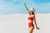 sexy a usmívající se žena v Santa klobouku a plavky s natažené ruce na pláži na Maledivách