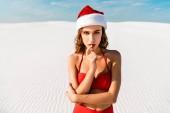 sexy žena v Santa klobouku a plavky při pohledu na kameru na pláži v Maledivách