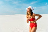 sexy and smiling woman in santa hat and swimsuit on beach in Maldives