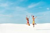 Fotografie sexy girlfriend and boyfriend in santa hats jumping on beach in Maldives