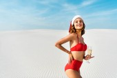 sexy and smiling woman in santa hat and swimsuit holding champagne glass on beach in Maldives