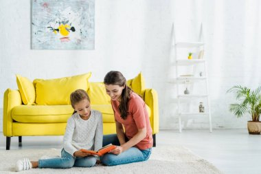 Happy kid reading book while sitting on carpet with babysitter stock vector