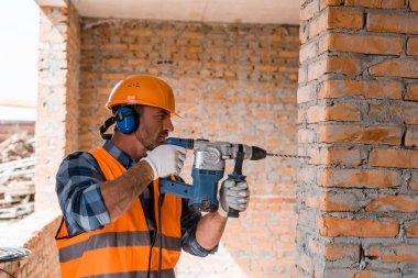 handsome bearded man using hammer drill near brick wall