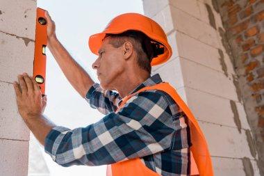 mature architect in helmet measuring concrete wall