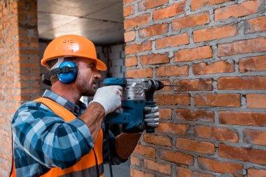 handsome constructor in helmet holding hammer drill