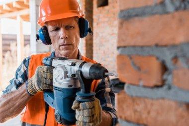 selective focus of mature man holding hammer drill near brick wall
