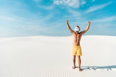 Sexy man in santa hat with virtual reality headset showing yes gesture on beach in Maldives stock vector