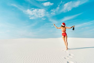 Back view of sexy woman in santa hat and swimsuit holding champagne glass and bottle on beach in Maldives stock vector