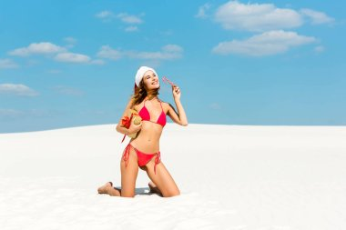Sexy and smiling woman in santa hat and swimsuit holding christmas gift and candy cane on beach in Maldives stock vector