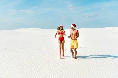 Sexy girlfriend and boyfriend in santa hats running on beach in Maldives stock vector