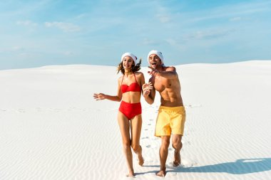 Sexy girlfriend and boyfriend in santa hats running and pointing finger on beach in Maldives stock vector