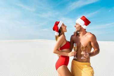 sexy girlfriend and boyfriend holding champagne glasses and hugging on beach in Maldives