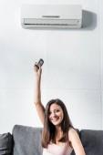 vonzó és mosolygós nő bekapcsolása légkondicionáló távirányítóval