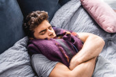 sick and handsome man in scarf with closed eyes lying in bed