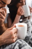 cropped view of sick girlfriend and boyfriend holding cups and sneezing with tea