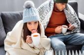 szelektív fókusz vonzó barátnő csésze tea bemelegítés mellett fűtőelem