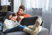selective focus of attractive girlfriend in sweater lying on knees of boyfriend