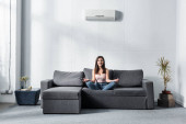 Photo attractive and smiling woman in lotus pose sitting on sofa
