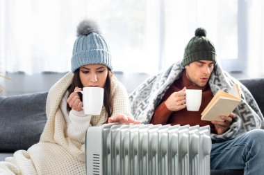 Attractive girlfriend with cup of tea and boyfriend reading book and warming up near heater stock vector