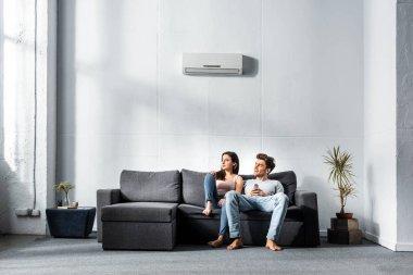 attractive girlfriend and handsome boyfriend sitting on sofa in apartment
