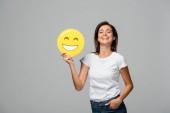 Kyjev, Ukrajina - 10. září 2019: veselá žena držící žlutě šťastně se usmívající emoji, izolovaná na šedi