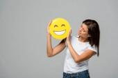 Kyjev, Ukrajina - 10. září 2019: atraktivní žena držící žlutě šťastně se usmívající emoji, izolovaná na šedi
