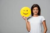 Kijev, Ukrajna - szeptember 10, 2019: gyönyörű mosolygós nő kezében sárga kacsintó emoji, elszigetelt szürke