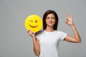 Kijev, Ukrajna - szeptember 10, 2019: gyönyörű nő gazdaság sárga kacsintó emoji és bemutató ok jel, elszigetelt szürke