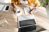 kivágott kilátás szabadúszó dolgozik laptop, notebook és kávé otthoni irodában