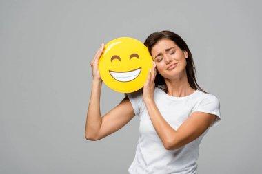 KYIV, UKRAINE - SEPTEMBER 10, 2019: emotional girl holding yellow happy smiling emoji, isolated on grey stock vector