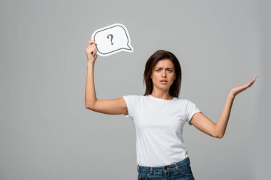 beautiful worried woman holding speech bubble with question mark, isolated on grey