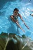 Fotografie selective focus of attractive woman in pearl necklace swimming in pool