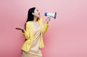 Photo side view of asian woman in yellow outfit screaming in megaphone isolated on pink