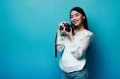 šťastný asijské žena v bílé halence drží digitální fotoaparát na modrém pozadí