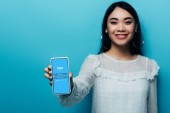 KYIV, UKRAINE - JULY 15, 2019: selective focus of smiling asian woman in white blouse holding smartphone with skype app on blue background