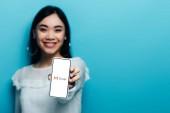Kyjev, Ukrajina - 15. července 2019: selektivní zaměření usměvavé asijky v bílé blůze držící smartphone s gmail aplikací na modrém pozadí