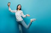 šťastná brunetka asijské žena pózování s kávou jít na modré pozadí