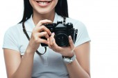 cropped view of smiling brunette asian woman taking picture on digital camera isolated on white