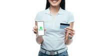 KYIV, UKRAINE - JULY 15, 2019: cropped view of smiling brunette asian girl holding credit card and smartphone with spotify app isolated on white