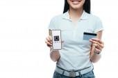 Kyjev, Ukrajina - 15. července 2019: oříznutý pohled usměvavé brunetky asijské dívky držící kreditní kartu a smartphone s uber aplikací izolovanou na bílém